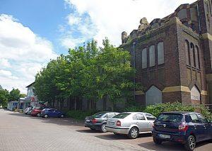 Die von Bäumen fast verdeckte Fassade der Lohnhalle, links ergänzt durch den auffallenden Neubau.
